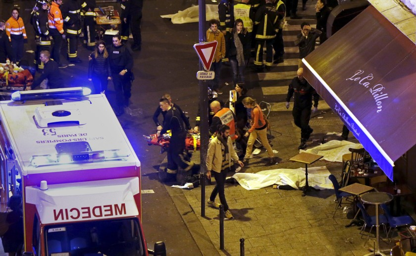 ATTENTION EDITORS - VISUAL COVERAGE OF SCENES OF INJURY French fire brigade members aid an injured individual near the Bataclan concert hall following fatal shootings in Paris, France, November 13, 2015. At least 30 people were killed in attacks in Paris and a hostage situation was under way at the concert hall in the French capital, French media reported on Friday. REUTERS/Christian Hartmann - RTS6W3I