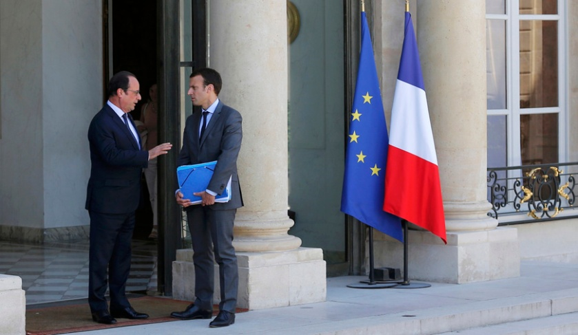 French President Francois Hollande (L) escorts French Economy Minister Emmanuel Macron as he leaves the Elysee Palace following the weekly cabinet meeting, in Paris, France, July 31, 2015. REUTERS/Stephane Mahe/File Photo